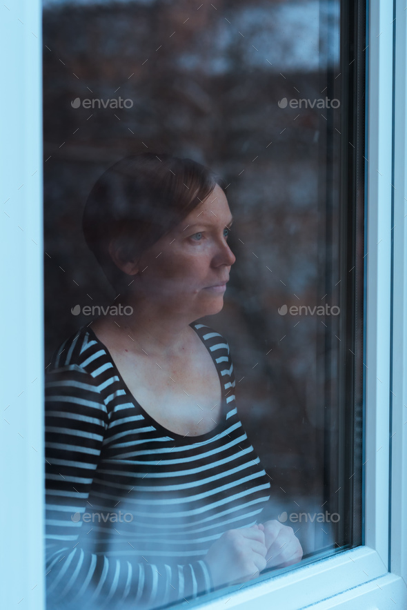 Depressed woman standing by the window and looking outside - Stock Photo - Images