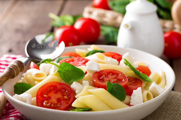 Pasta salad with fresh red cherry tomato and feta cheese. Italian cuisine - Stock Photo - Images