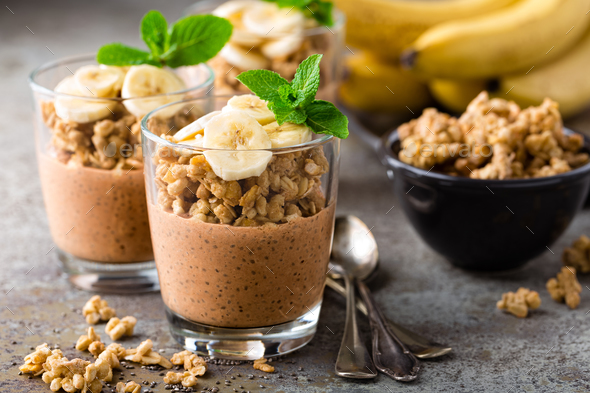 Layered chocolate chia pudding parfait with banana, granola and yogurt, dessert - Stock Photo - Images