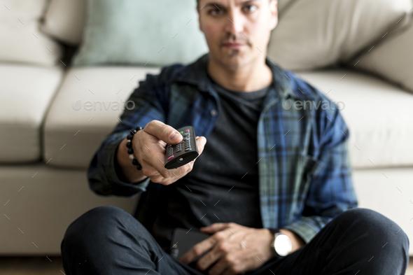 Caucasian man using remote tv controller - Stock Photo - Images