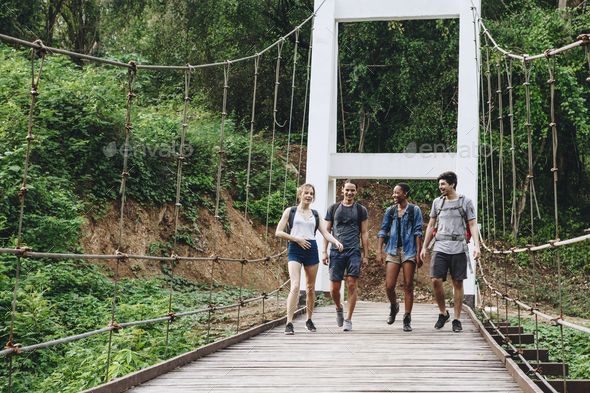 Group of friends walking on the bridge in a tropical countryside adventure and journey concept - Stock Photo - Images