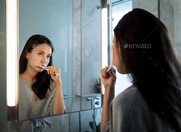 Woman brushing her teeth in the morning - Stock Photo - Images