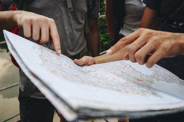 Group of friends looking at a map together travel and teamwork concept - Stock Photo - Images