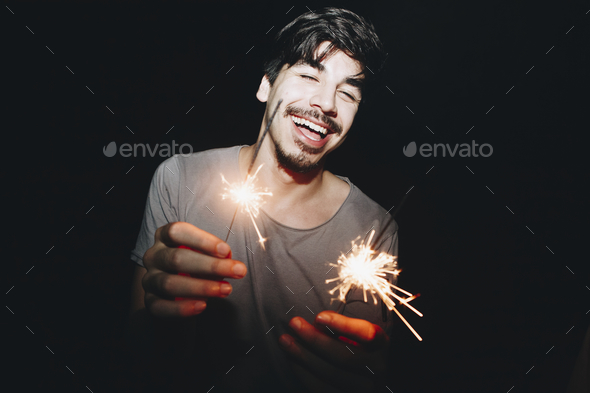 Caucasian man playing with sparklers celebration and festive party concept - Stock Photo - Images