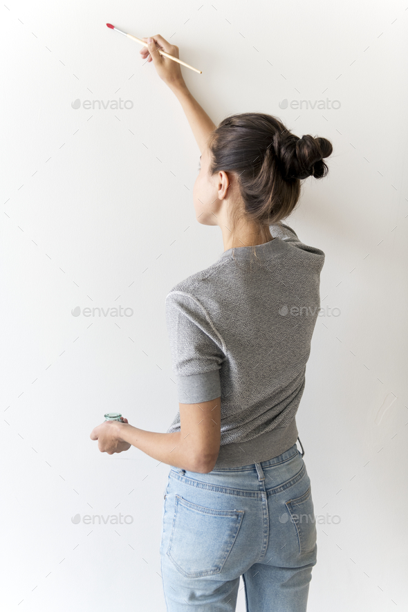 Artist woman painting the wall - Stock Photo - Images
