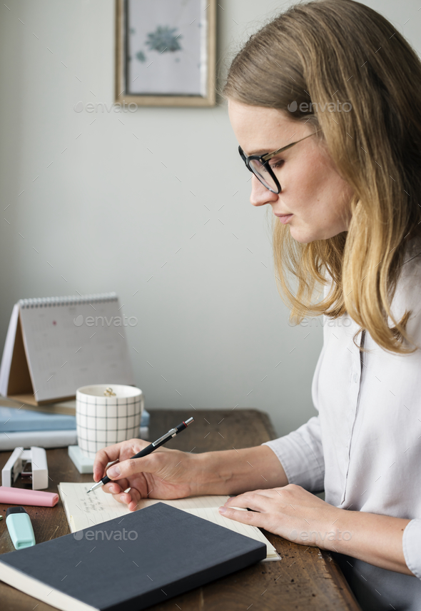 Caucasian woman writing a note - Stock Photo - Images