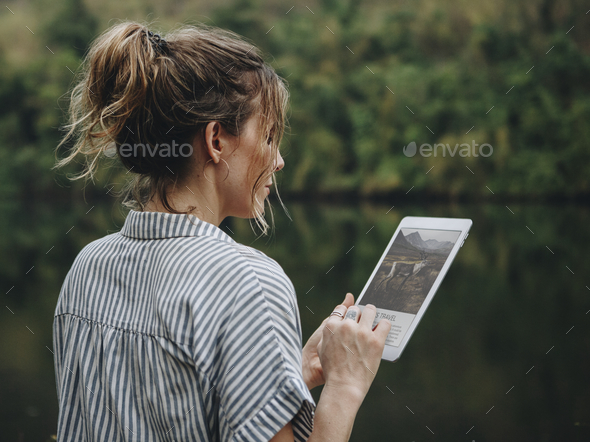 Woman alone in nature using a digital tablet internet connection and travel concept - Stock Photo - Images