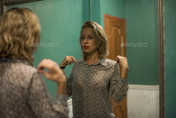 Blond woman getting ready in a restroom - Stock Photo - Images