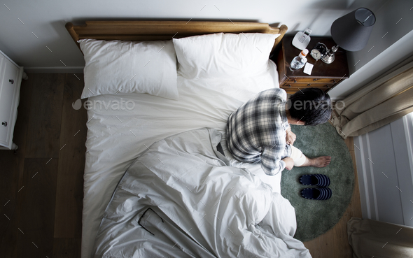 Injured Asian man sitting on the bed - Stock Photo - Images