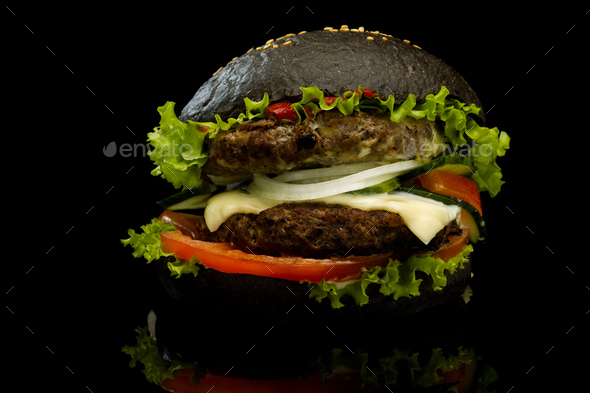 Black burger on a black background - Stock Photo - Images