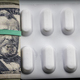 Dollar bills along with white pill package, conceptual image co-payment health - PhotoDune Item for Sale