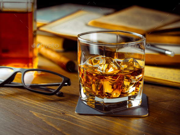 Whiskey on the rocks and scholar books - Stock Photo - Images