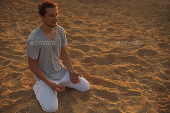 Shot of healthy young man standing in yoga pose on the sand. - Stock Photo - Images