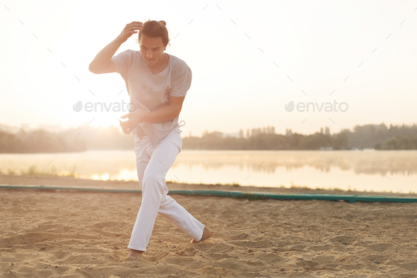 Athletic capoeira performer making movements on the beach - Stock Photo - Images