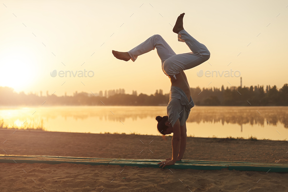 Athletic yoga man workout training on the beach sunrise - Stock Photo - Images