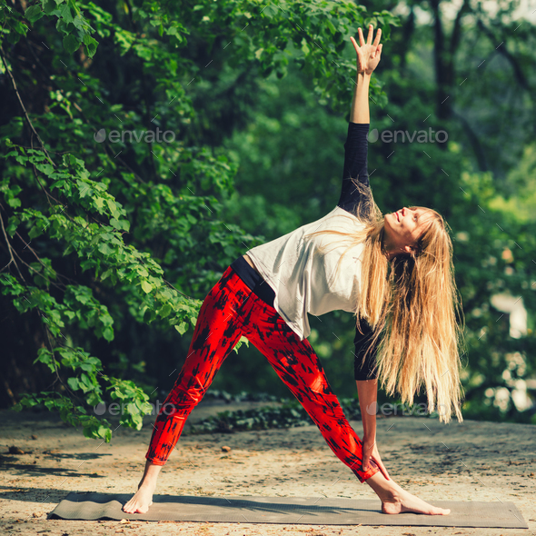 Pretty young woman doing yoga in the park - Stock Photo - Images