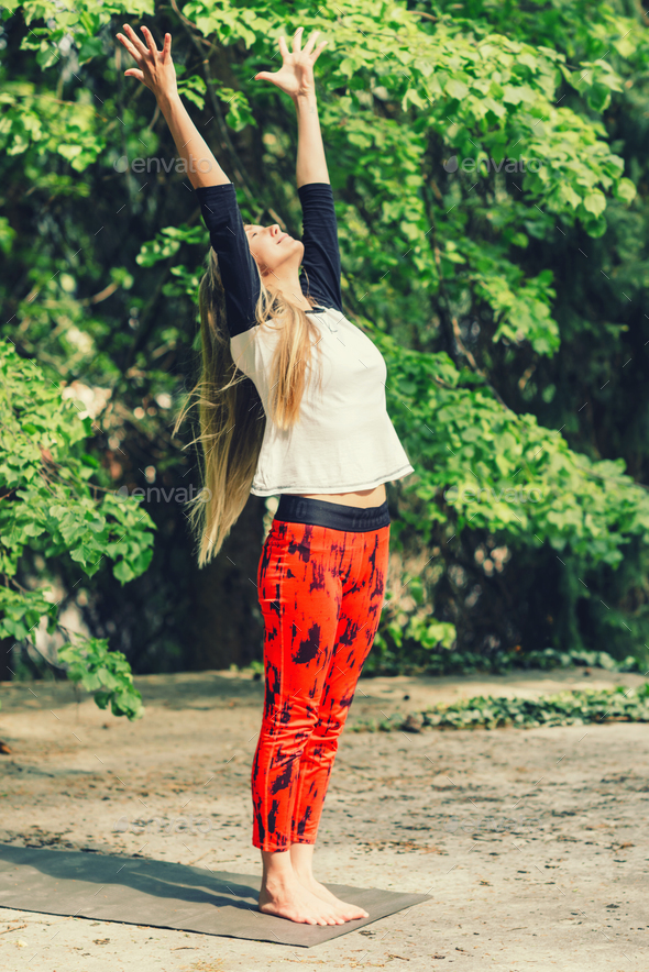 Attractive blond woman doing yoga outdoors - Stock Photo - Images