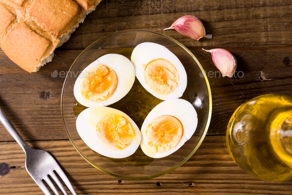 hard boiled eggs cut in half with oil and vinegar, on wooden board - Stock Photo - Images