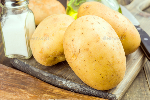 whole unpeeled potatoes without cooking, rustic wooden stage - Stock Photo - Images