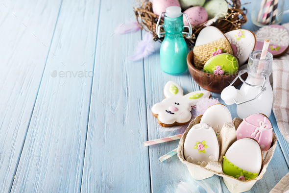 Easter cookies egg in the paper box with milk in glass on wood background - Stock Photo - Images