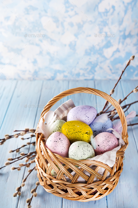 Easter basket filled with colorful eggs on a blue background - Stock Photo - Images