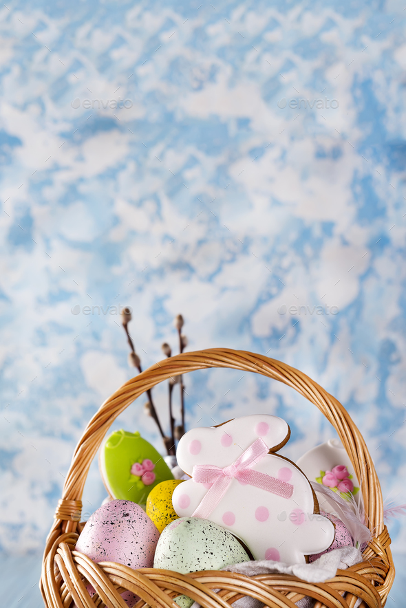 Easter cookies, bunnies and Multicolored Easter eggs in a basket on light blue background - Stock Photo - Images