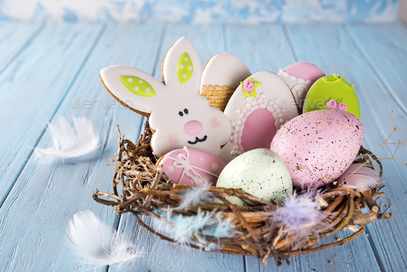 Colorful easter egg end easter cookies as rabbit and egg in the nest on wood background - Stock Photo - Images