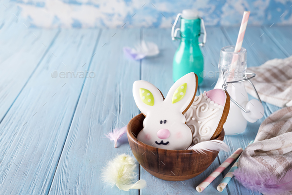 Easter cookies as rabbit and egg in the wooden bowl with milk in glass on wood background - Stock Photo - Images