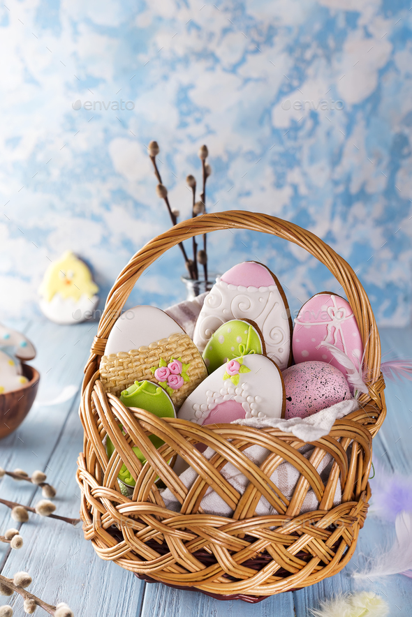Decorated Easter Cookies in wooden basket on a blue wooden background - Stock Photo - Images