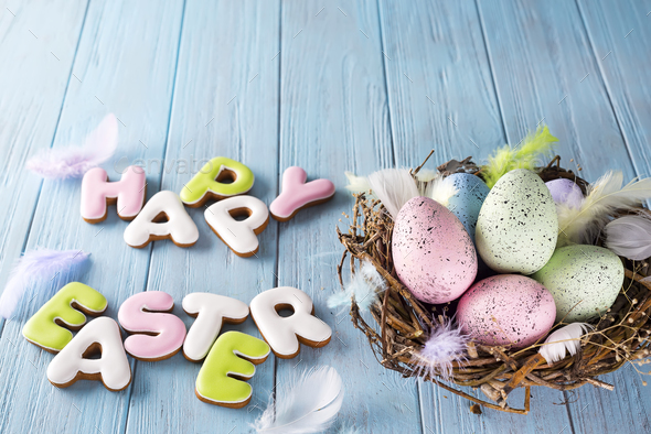 Colorful easter egg end cookies letter Happy Easter in the nest on wood background - Stock Photo - Images