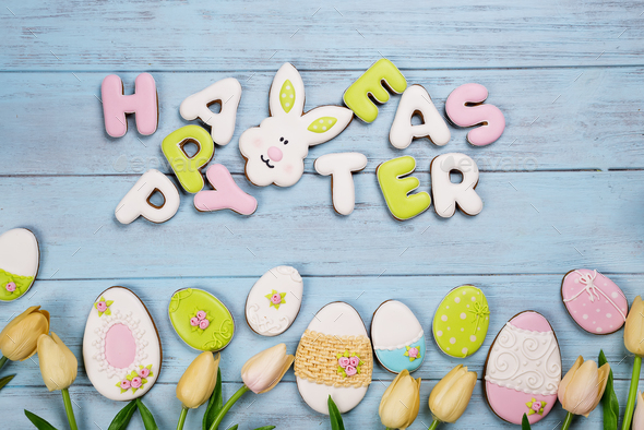Easter cookies letter Happy Easter and colorful eggs with tulips on wood background - Stock Photo - Images