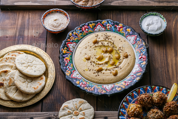 Hummus, chickpea, falafel with tahini, yoghurt and pita in traditional plate - Stock Photo - Images