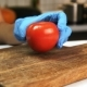 Woman Cuts Tomato in Half with Knife in Kitchen of House - VideoHive Item for Sale