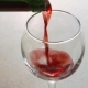 Man Pours Red Wine Into Glass Standing on Table in Kitchen - VideoHive Item for Sale