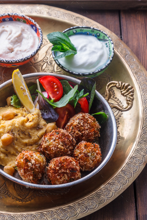 Hummus, falafel, salad in a pan with yoghurt and tahini - Stock Photo - Images