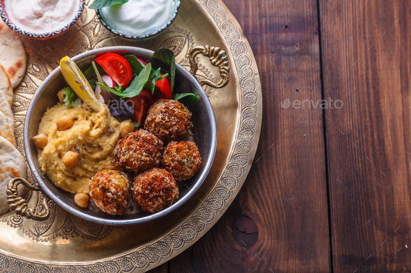 Hummus, falafel, salad and pita in a copper pan, copyspace - Stock Photo - Images
