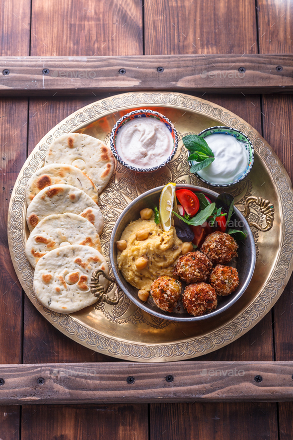 Hummus, falafel, salad and pita in a copper pan - Stock Photo - Images