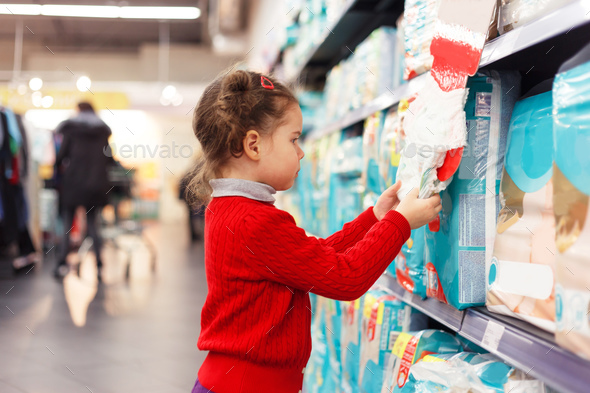 Little girl selects diapers in supermarket - Stock Photo - Images