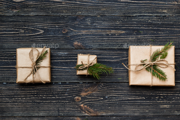 Three Vintage gift boxes with spruce branches on wooden background - Stock Photo - Images