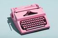 Pink typewriter on a blue pastel background. - PhotoDune Item for Sale