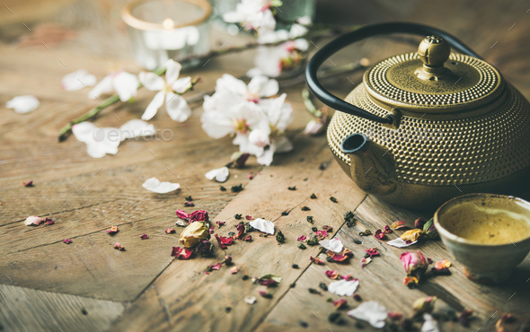 Iron teapot, cups, dried rose buds, blooming almond flowers, candles - Stock Photo - Images