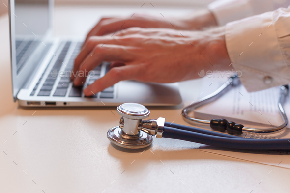 Doctor working with laptop computer in medical workspace office. Focus on stethoscope - Stock Photo - Images