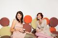 beautiful caucasian girls on colorful sofa - PhotoDune Item for Sale