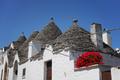Trulli houses with geranium flowers in Alberobello - PhotoDune Item for Sale