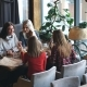 Group of Four Young People Sitting at Table in Restaurant and Having Fun While Dining. - VideoHive Item for Sale
