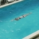 Girl Swims in the Outdoor Pool at the Hotel in a Black Swimsuit - VideoHive Item for Sale