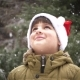 a Child in a Santa Claus Hat Rejoices in the Falling Snow - VideoHive Item for Sale