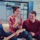 Group of Young Hipster Friends Sitting on the Couch and Playing Guitar and Singing Songs - VideoHive Item for Sale