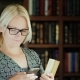 A Woman in Glasses Uses a Smartphone in the Library, Holds Books in Her Hand. Against the Background - VideoHive Item for Sale