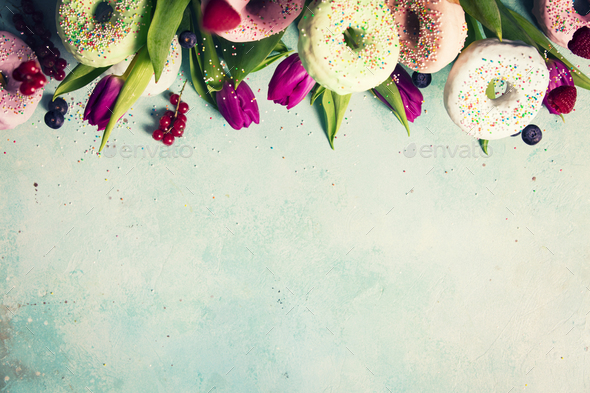 Sweet and colourful doughnuts with sprinkles, purple tulips and - Stock Photo - Images